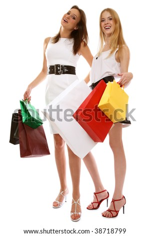 Two slim stylish young smiling girls with shopping bags, over white background