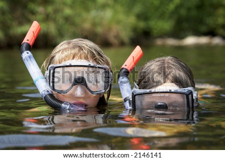 two small and young children playing at the river on a warm sunny day. they are wearing snorkling equiptment and are in the water - stock photo
