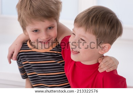 two small boys best friends. Two brother huging each other, smiling and laughing  - stock photo