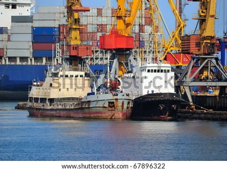 Two small cargo vessels and a big container ship behind them in the port of Odessa, Black Sea