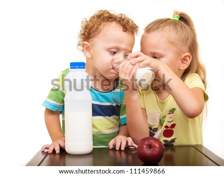 two small children drinking milk from a glass
