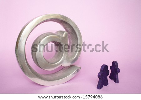 Two small figures in front of arroba in pink background - stock photo