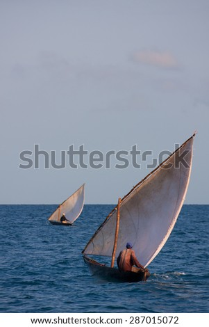 two small fishing boats heading out into the open ocean with billowing sails in a strong wind - stock photo