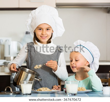 Two small girls eating healthy oatmeal at home kitchen