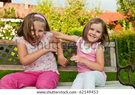 Two small girls (sisters) larking in backyard sitting on bench - stock photo
