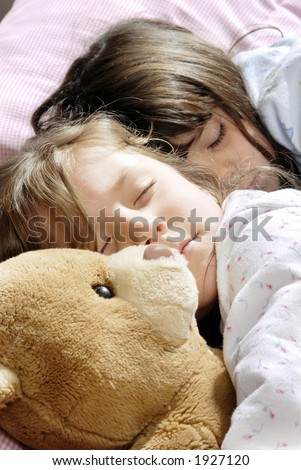 two small girls sleeping with a plush bear - stock photo