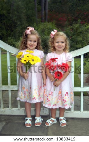 Two small girls stand side by side in front of a wooden garden gate.  They are holding yellow and pink daisy bouquets. - stock photo