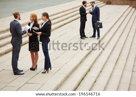 Two small groups of business people interacting outside - stock photo