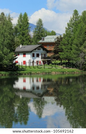 Two small house reflecting in the white lake by summer, Crans Montana, Switzerland - stock photo
