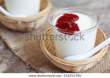 Two small jars homemade yogurt with raspberry jam in a wicker baskets on a wooden table, selective focus - stock photo