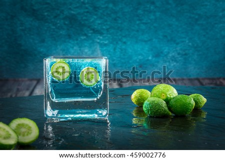Two small limes immersed in an effervescent liquid - stock photo