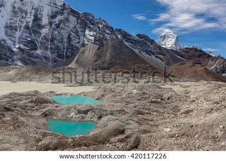 Two small moraine lakes of turquoise color and snowy mountain peaks on the horizon. Bright blue moraine lakes at the foot of the Imja Glacier, Himalayas, Nepal. Near Island Peak base camp. - stock photo