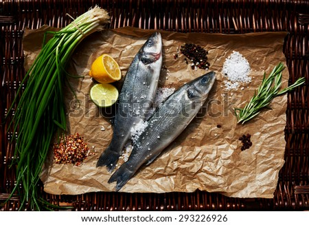 Two small sea bass fish shop on the counter, put them on parchment paper - stock photo