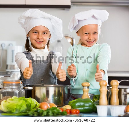 Two small smiling happy girls cooking vegetable soup at home kitchen - stock photo