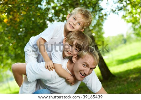 Two small sons piggyback on the daddy - stock photo