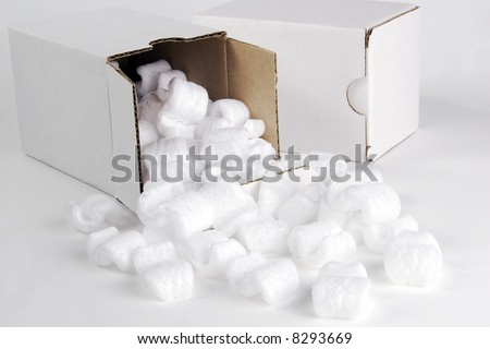 Two small white cardboard packing boxes.  White styrofoam packing peanuts are spilling from the open box. - stock photo