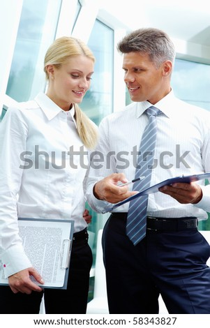 Two smart employees discussing new strategy at meeting - stock photo