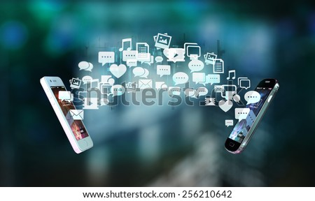 Two smart phones exchanging messages and multimedial content visualized by icon flow - stock photo