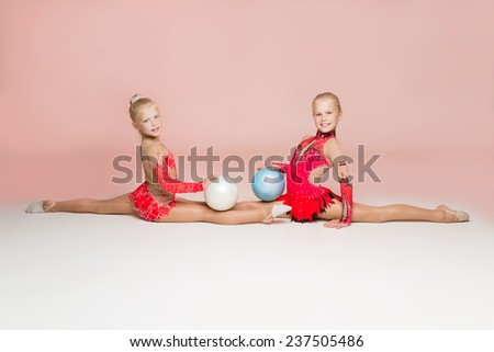 Two smiley gymnasts posing with balls on light pink background - stock photo