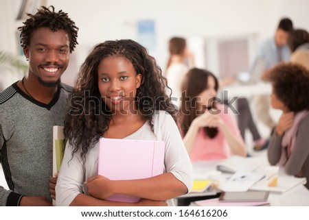 Two smiling African college students standing in front of thier peers. - stock photo