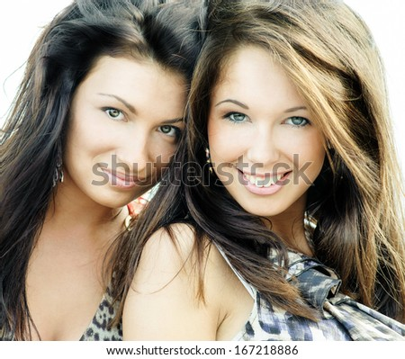 Two smiling attractive girl friends - blond and brunette
