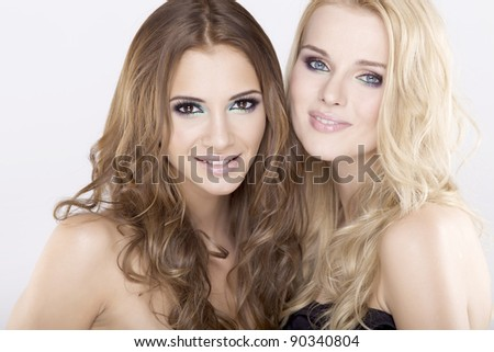 Two smiling attractive girl friends - blond and brunette on white background - stock photo