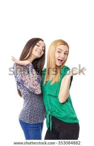 Two smiling attractive teenage girls - blonde and brunette-posing  on white background - stock photo