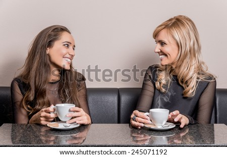 Two smiling attractive women having a cup of coffee in a coffee shop. - stock photo