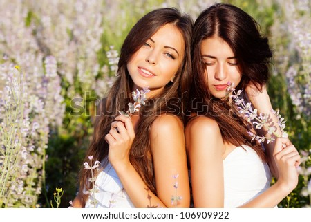 two smiling beautiful brunettes in the flowers  field - stock photo
