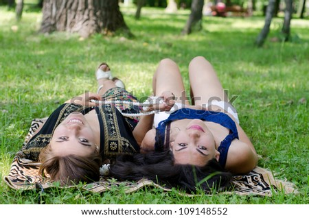 two smiling beautiful girlfriend lying on the grass - stock photo
