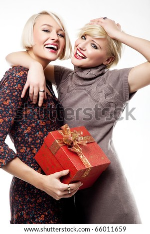 Two smiling blond beauties holding a christmas present - stock photo