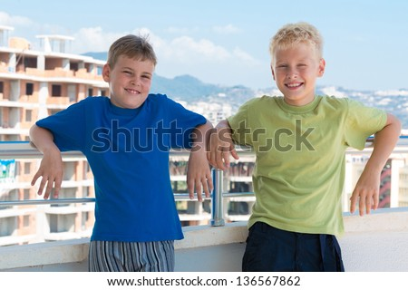 Two smiling boys in colored T-shirts are on the background of building under construction - stock photo