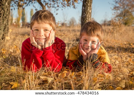 Two smiling boys lying down on withered grass in autumn park