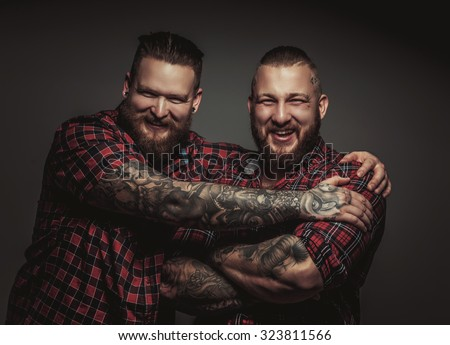 Two smiling brutal bearded males with tattooed arms isolated on grey background. - stock photo
