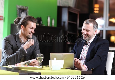 Two smiling business men eat at restaurant