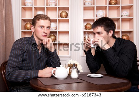Two smiling business men speaking about deal at restaurant on lunch break - stock photo
