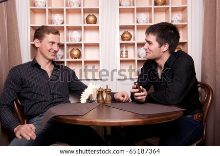 Two smiling business men speaking about deal at restaurant on lunch break