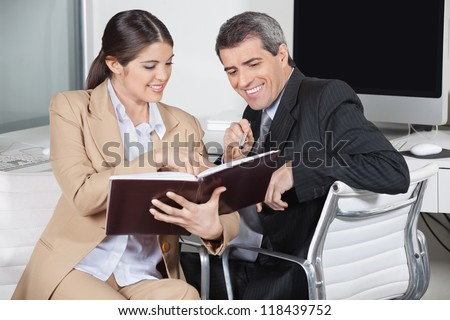 Two smiling business people looking in an appointment book in the office - stock photo