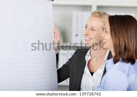 Two smiling businesswoman standing by flipchart in office - stock photo