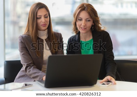 Two smiling businesswoman working together.