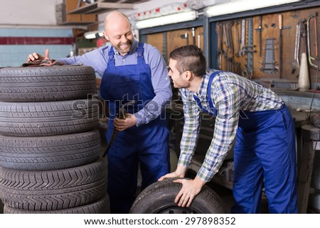 Two smiling car mechanics working together at workshop. Focus on brunet