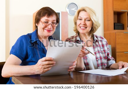 Two smiling colleagues discussing the contents of the documents - stock photo