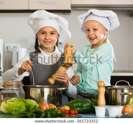 Two smiling cute little sisters in caps learning how to cook at home kitchen