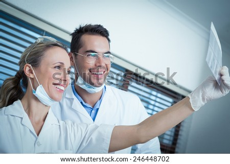 Two smiling dentists looking at x-ray - stock photo