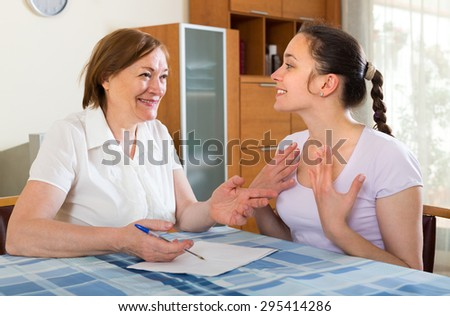Two smiling females with financial documents at table in home interior. Selective focus