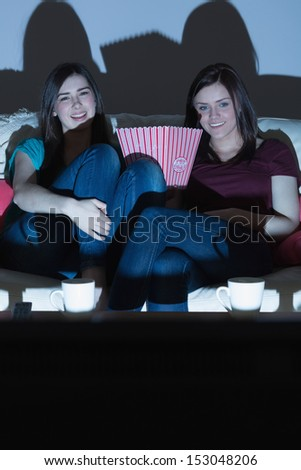 Two smiling friends on the couch watching tv together in the dark at home in the living room