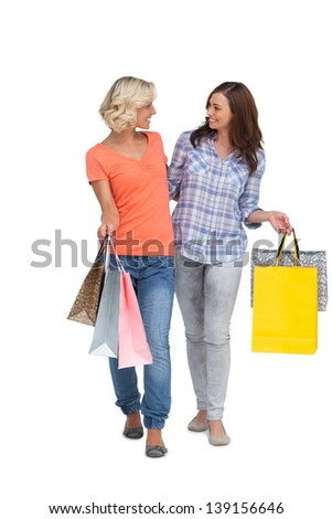 Two smiling friends with shopping bags on white background - stock photo