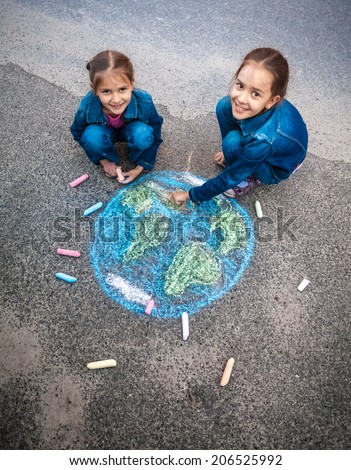 Two smiling girls drawing Earth with chalks on street - stock photo