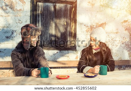 Two smiling girls drinking hot tea sunny winter day in the countryside. Cross process vintage soft focus. - stock photo