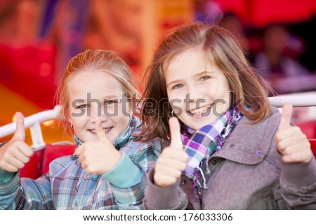Two smiling girls giving the thumbs up with both hands.